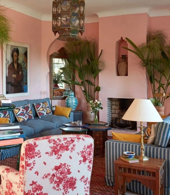 an eclectic living room with light pink walls, blue and white striped furniture, potted plants and a Moroccan lamp