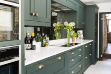 an elegant hunter green kitchen with white countertops, a mirror tile backsplash and touches of brass