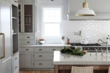 an elegant light grey kitchen with chic gold handles, a white subway tile backsplash, white countertops and white pendant lamps