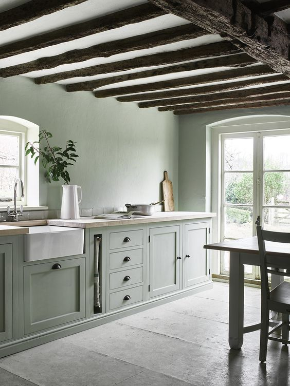 an ethereal modern farmhouse kitchen in pale green, with butcherblock countertops, with wooden beams and much natural light