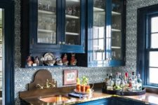 an exquisite kitchen in classic blue, with a patterned tile backsplash, wooden countertops and a gold pendant lamp