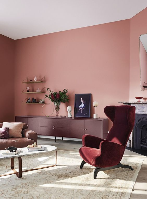 an exquisite living room with pink walls, a burgundy velvet chair and a burgundy credenza, a brown sofa and a fireplace