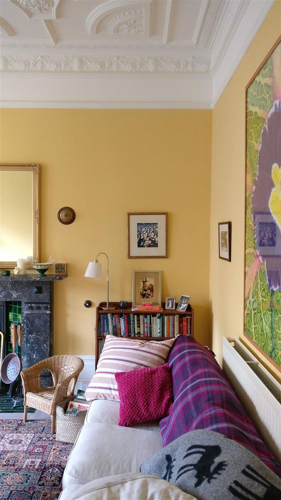 an exquisite living room with warm yellow walls, colorful textiles and vintage furniture plus a stone clad fireplace