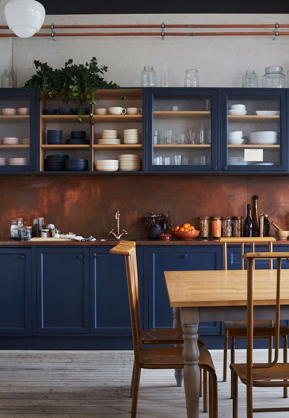 an impressive blue kitchen with a copper backsplash and a rich stained wooden countertop feels refined and vintage-inspired
