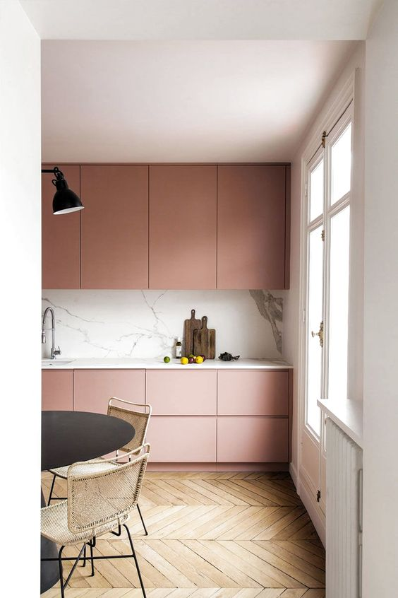 an ultra-minimal dusty rose kitchen with sleek cabinets, a white marble backsplash and countertops plus touches of black