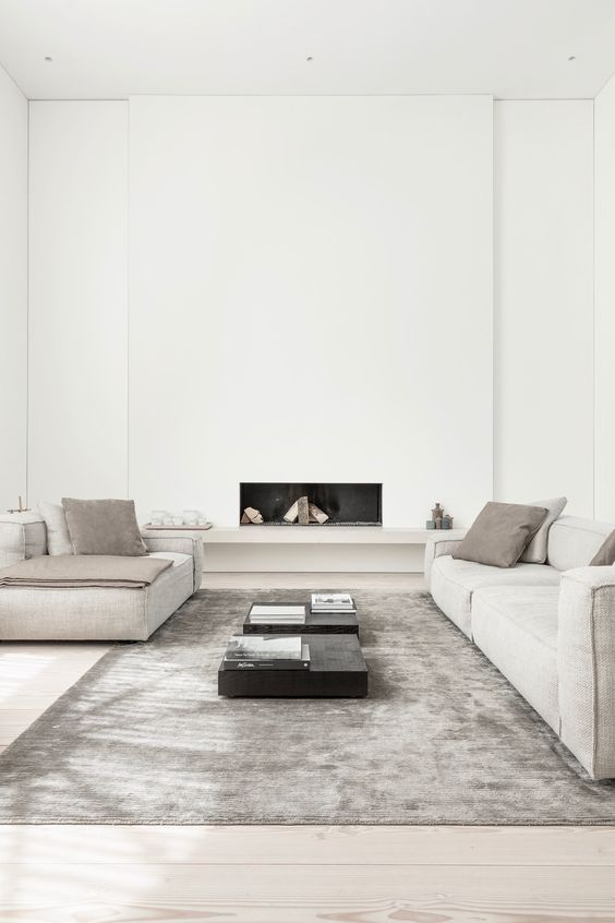 an ultra minimal living room in neutrals, with a built in fireplace, neutral furniture, black tables and a grey rug