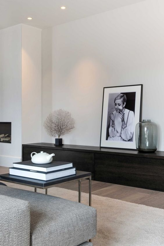 an ultra minimal living room with a dark stained storage unit, a grey sofa, a black table and a statement artwork