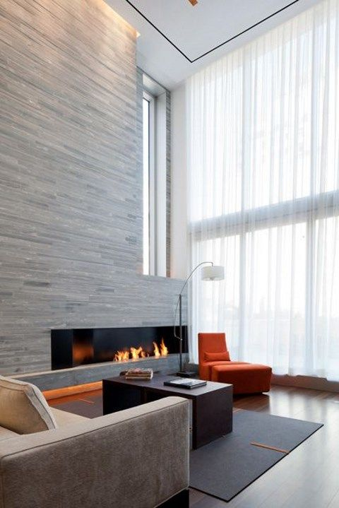 an ultra-minimalist living room with a stone wall with a built-in fireplace, a bright orange chair, a glazed wall and some comfy furniture