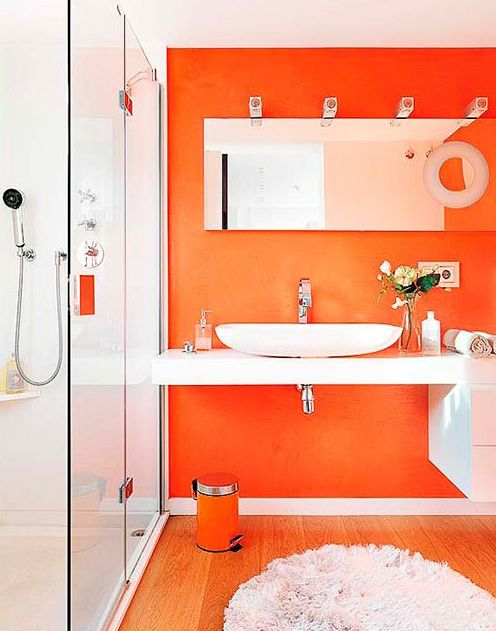 a bright and fresh modern bathroom with an orange accent wall and some more touches and all whites for a contrast is wow
