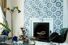 02 a built-in vintage fireplace clad with blue and white patterned tiles that stand out and make the space more refined
