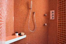 03 a bright burnt orange bathroom clad with small scale tiles and white pebbles on the floor is refined