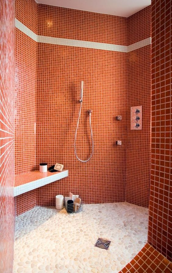 a bright burnt orange bathroom clad with small scale tiles and white pebbles on the floor is refined