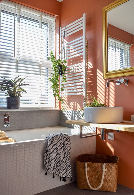 a bright burnt orange bathroom with a white tile clad bathtub and other white touches to refresh the space