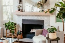 04 a built-in fireplace with grey and white patterned tiles around and up to the ceiling and a simple wooden mantel