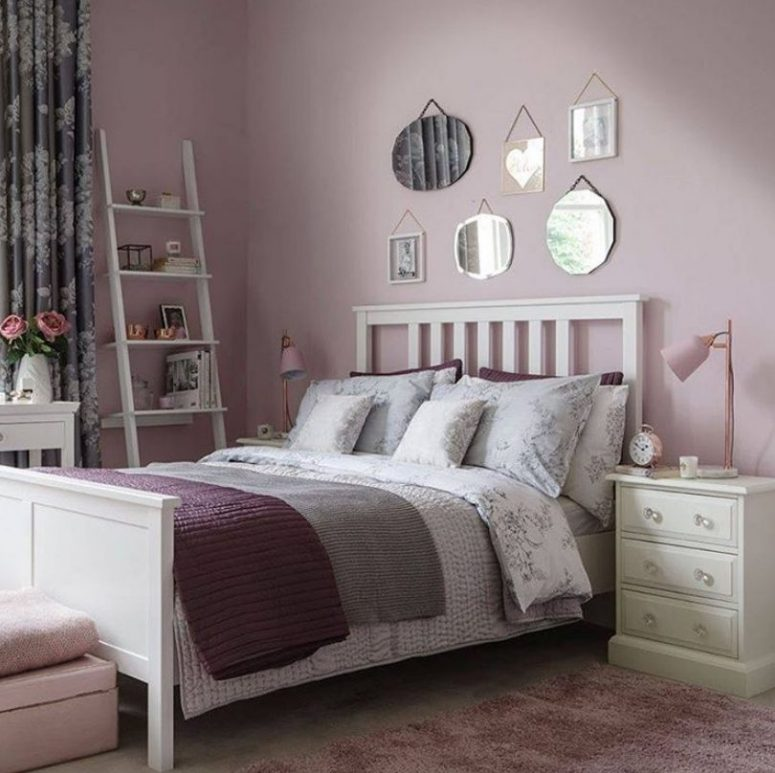 a cozy and romantic bedroom with lilac walls, a mirror gallery wall, purple and floral bedding and neutral furniture