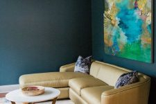 04 a dark nook is lit up with a neutral colored sofa and a super bright abstract artwork over it