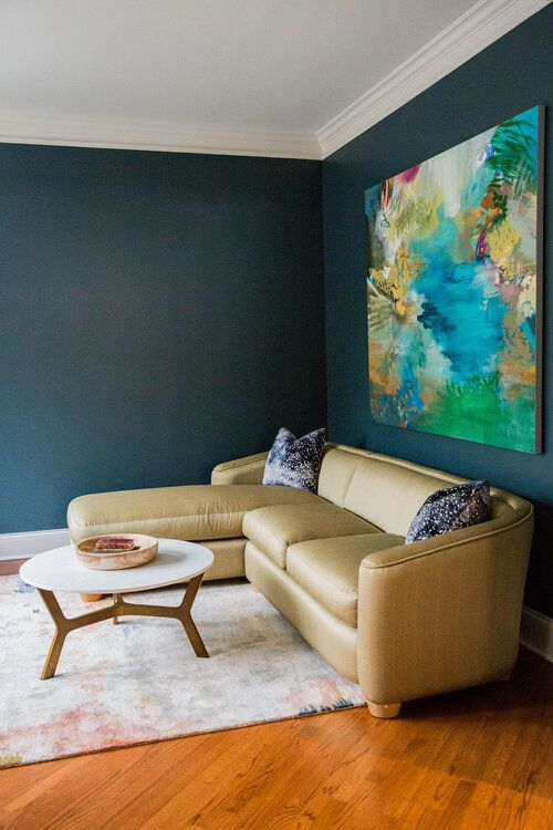 a dark nook is lit up with a neutral colored sofa and a super bright abstract artwork over it