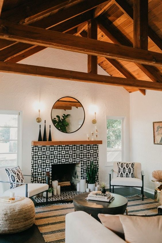 a bright monochromatic mid century boho living room with a fireplace clad with black and white graphic tiles and a wooden mantel