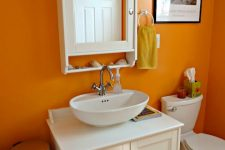 05 a bright orange bathroom with bold walls and all white everything to make the space feel fresh and cool