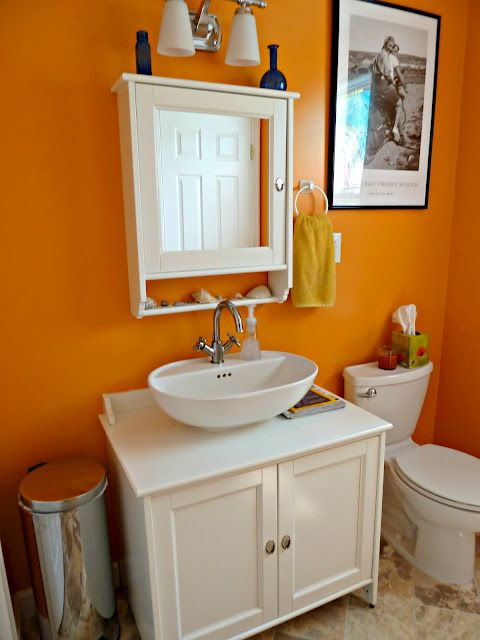 a bright orange bathroom with bold walls and all white everything to make the space feel fresh and cool