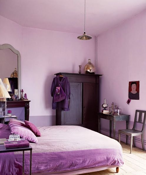 a lilac and purple bedroom with color block walls, vintage furniture, monochromatic purple bedding and metallic touches
