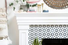 06 a built-in fireplace clad with black and white graphic tiles and with a refined white mantel and frame around it