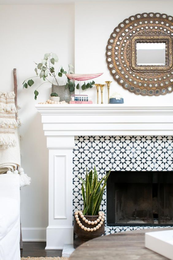 a built-in fireplace clad with black and white graphic tiles and with a refined white mantel and frame around it