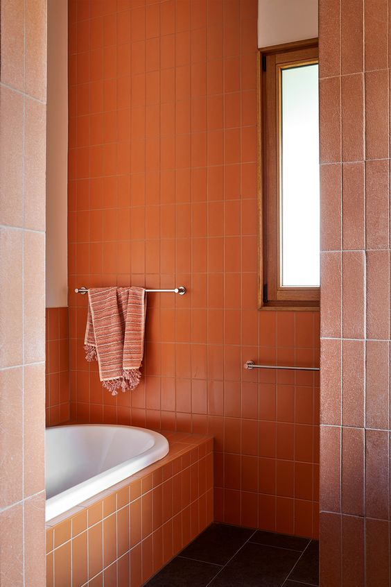 a burnt orange modern bathroom clad with skinny tiles is a lively and cheerful space to have in your home