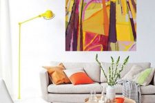 06 a neutral living room with a super bold artwork that takes over it and a bold lamp and pillows that echo with it