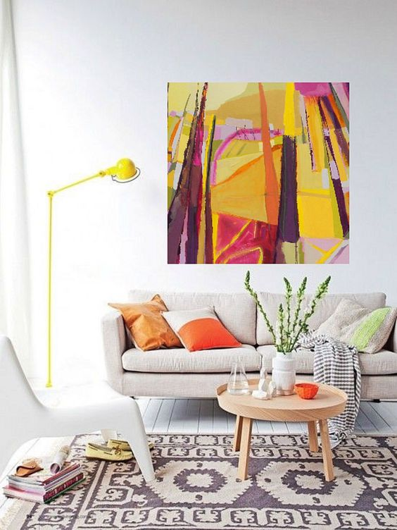 a neutral living room with a super bold artwork that takes over it and a bold lamp and pillows that echo with it
