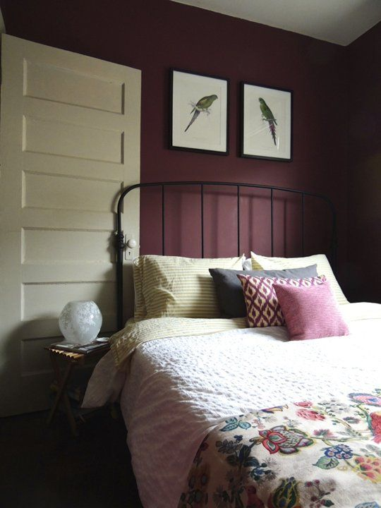 a refined vintage bedroom with plum-colored walls, a black forged bed, colorful printed bedding and cute artworks