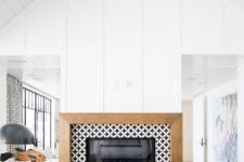 07 a built-in fireplace clad with black and white graphic tiles around and with a wooden frame for a contemporary space