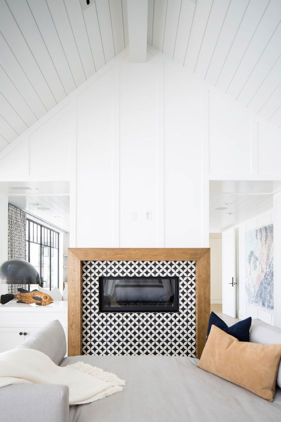 a built-in fireplace clad with black and white graphic tiles around and with a wooden frame for a contemporary space