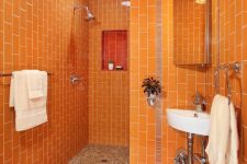 07 a cheerful orange bathroom clad with vertical tiles, with built-in lights and white appliances