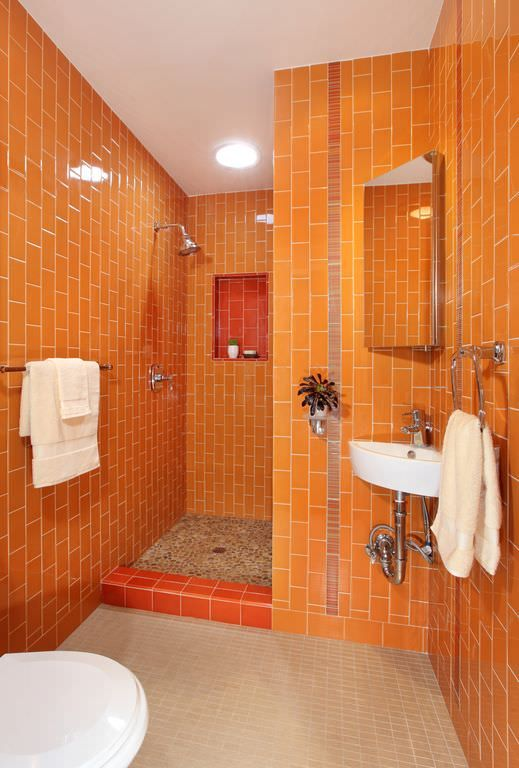 a cheerful orange bathroom clad with vertical tiles, with built-in lights and white appliances