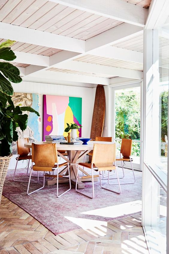 a mid century modern dining space with super bright abstract artworks that create a mood here