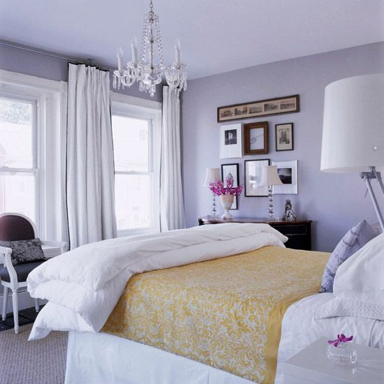 a refined classic bedroom with lilac walls, a crystal chandelier, neutral and lilac bedding and a stylish gallery wall