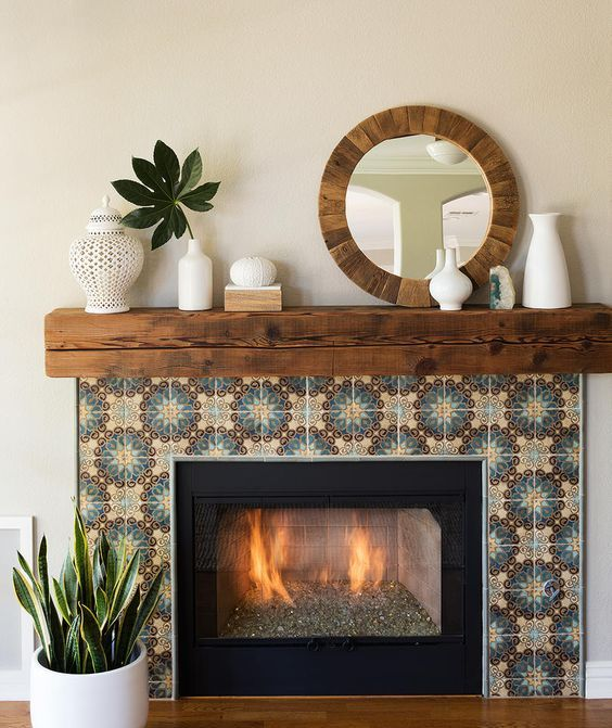 a built in fireplace clad with colored patterned tiles around, with a rich stained wooden slab mantel