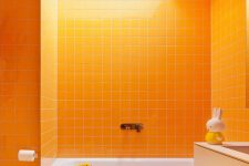 08 a fun and vibrant orange bathroom clad with tiles, with a tan vanity and a skylight for more cheerfulness