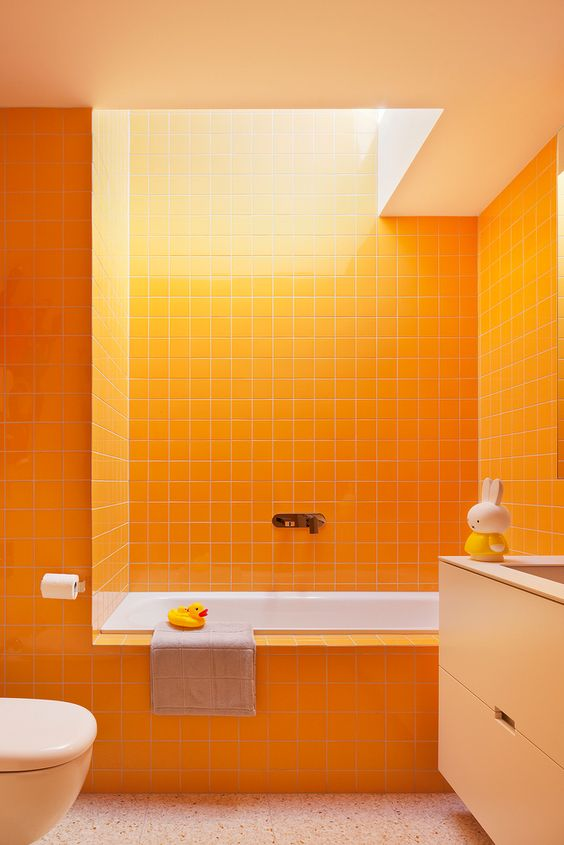 a fun and vibrant orange bathroom clad with tiles, with a tan vanity and a skylight for more cheerfulness