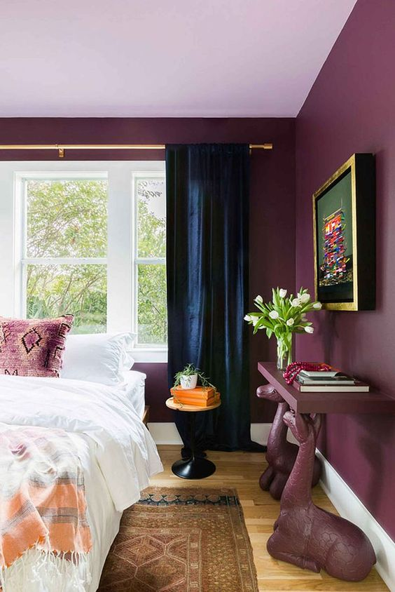 a modern maximalist bedroom with purple walls, a crazy console table and pillows, navy curtains and a bold artwork