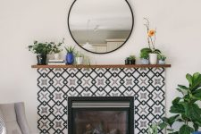 09 a built-in fireplace surrounded with black and white geometric tiles and with a stained wooden mantel with plants in pots