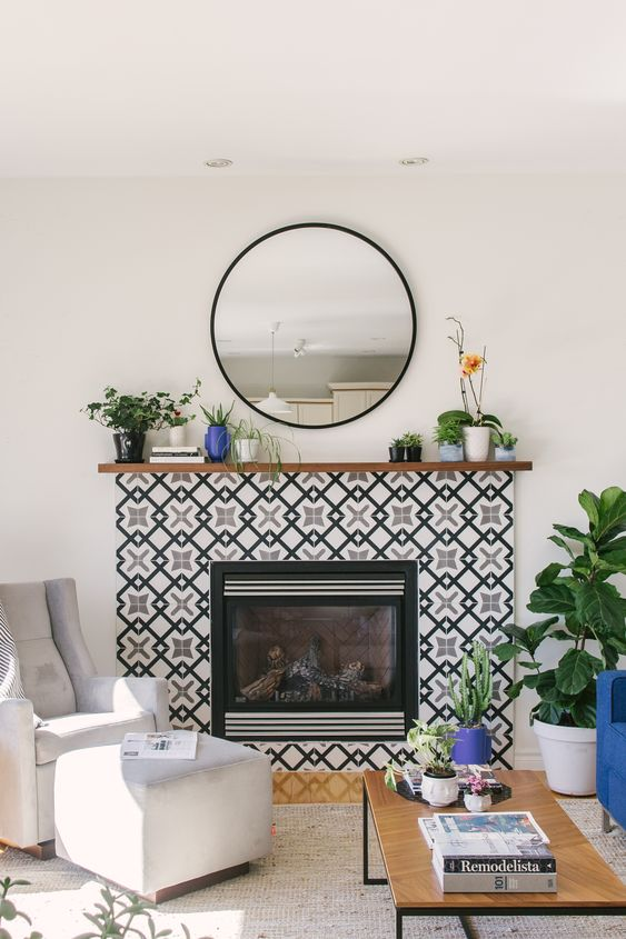 a built-in fireplace surrounded with black and white geometric tiles and with a stained wooden mantel with plants in pots