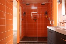 09 a refined modern bathroom in orange and chocolate brown, with long tiles and a chic vanity plus white appliances