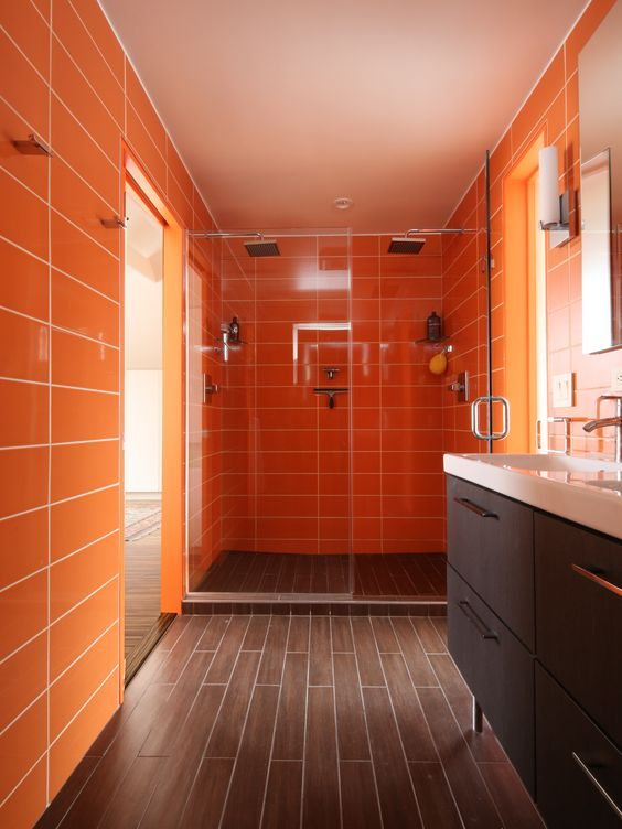 a refined modern bathroom in orange and chocolate brown, with long tiles and a chic vanity plus white appliances