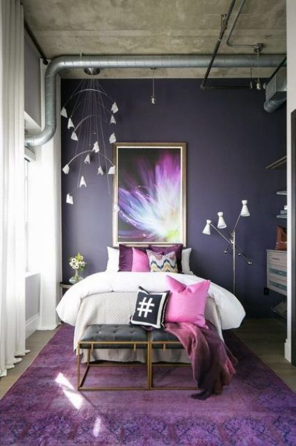 a super bold modern and industrial bedroom with a deep purple accent wall and matching pillows and a rug, unusual lamps and a statement artwork