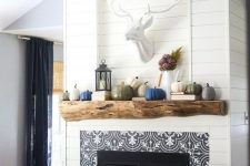 10 a built-in fireplace with black and white patterned tiles, a rough wood mantel over the fireplace is a perfect match for a rustic living room