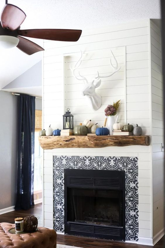 a built-in fireplace with black and white patterned tiles, a rough wood mantel over the fireplace is a perfect match for a rustic living room