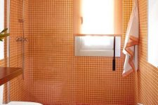 10 a simple modern bathroom in white and orange, with small size tiles in the shower and orange textiles
