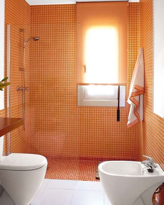 a simple modern bathroom in white and orange, with small size tiles in the shower and orange textiles
